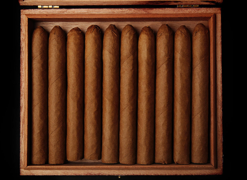 Cigars neatly lined within a humidor, ready for smoking.