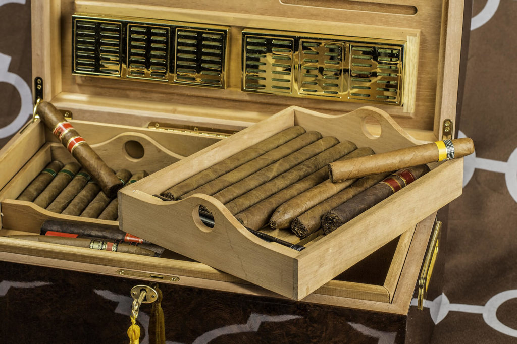 A large and grand humidor sits full of high quality cigars.