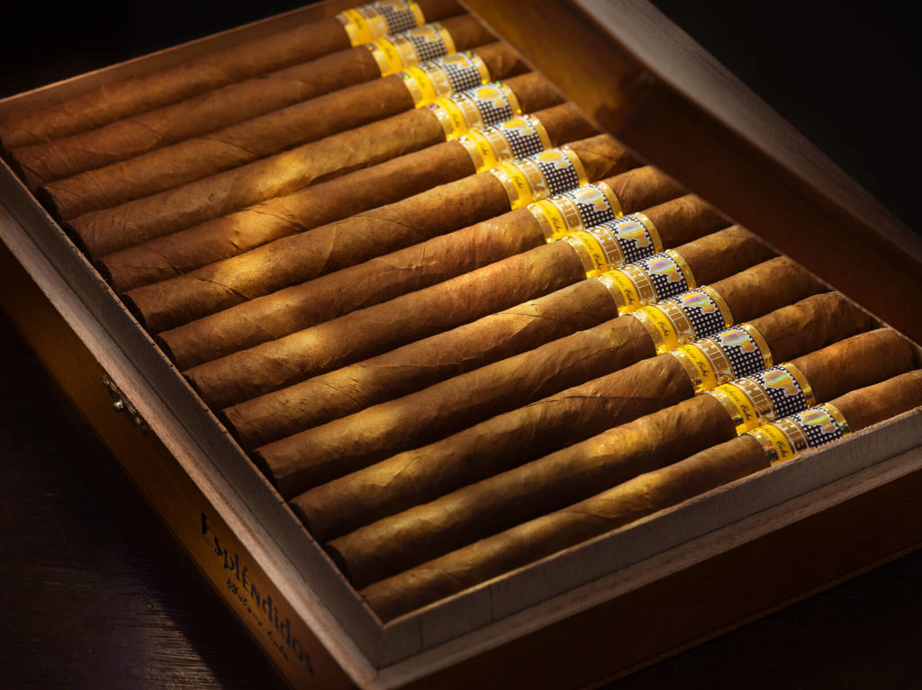 A row of cigars, neatly stored in a humidor.