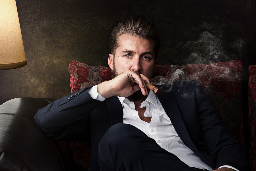 A young man sits in a chair while enjoying a fine cigar.