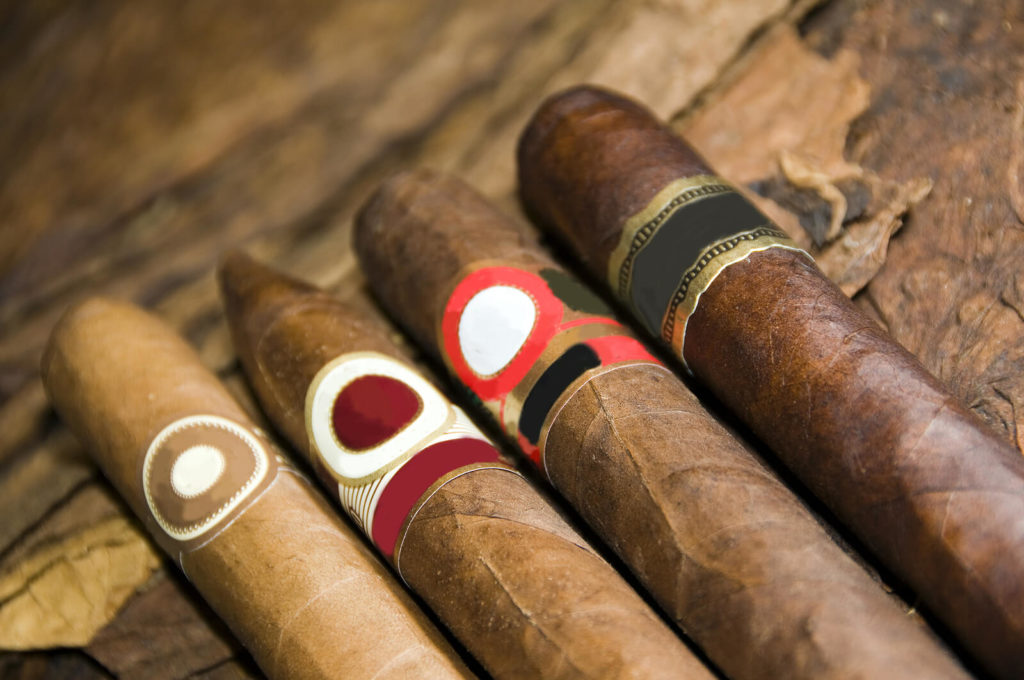 A variety of cigars laid out on a table.